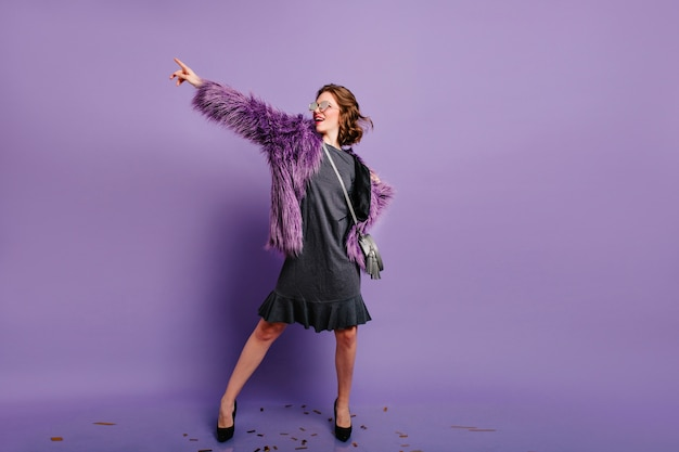 Retrato de corpo inteiro de uma mulher encantadora e glamourosa dançando com uma jaqueta roxa de inverno