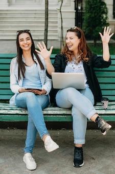 Retrato de corpo inteiro de uma mulher encantadora sentada em um banco, enquanto mulheres de tamanho grande com cabelo encaracolado estão contando histórias enquanto seguram um laptop.
