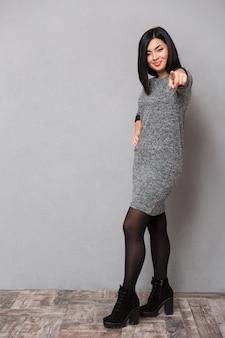 Retrato de corpo inteiro de uma mulher feliz apontando o dedo para a frente na parede cinza