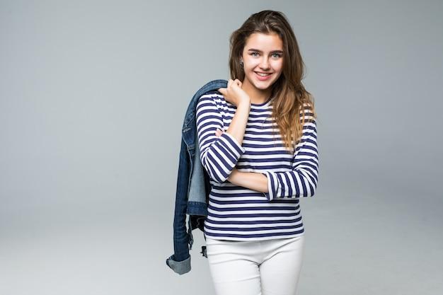Retrato de corpo inteiro de uma mulher feliz, apontando o dedo para longe em um fundo branco