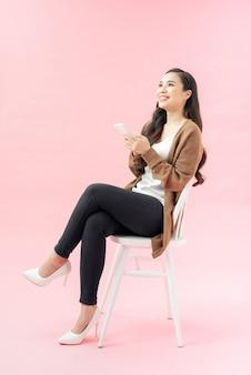 Retrato de corpo inteiro de uma mulher feliz e casual sentada na cadeira e usando o smartphone isolado no fundo rosa