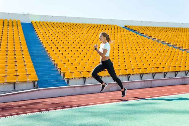 Retrato de corpo inteiro de uma mulher fitness correndo no estádio
