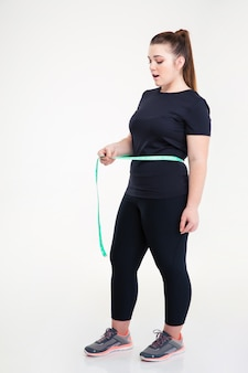 Retrato de corpo inteiro de uma mulher gorda medindo a cintura, isolado em uma parede branca