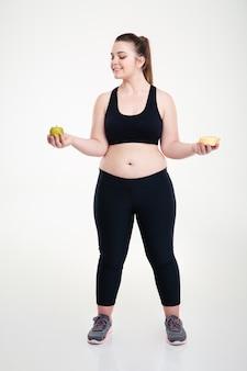 Retrato de corpo inteiro de uma mulher gorda sorridente escolhendo entre donut e maçã isolado em uma parede branca