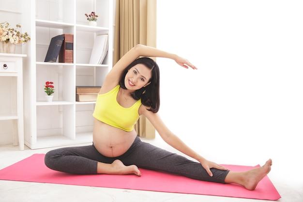 Retrato de corpo inteiro de uma mulher grávida saudável e feliz fazendo ioga, alongamento em casa