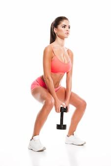 Retrato de corpo inteiro de uma mulher jovem fitness fazendo agachamento