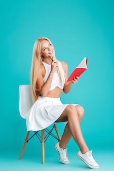 Retrato de corpo inteiro de uma mulher loira feliz furando o caderno e sentada na cadeira, isolada no fundo azul