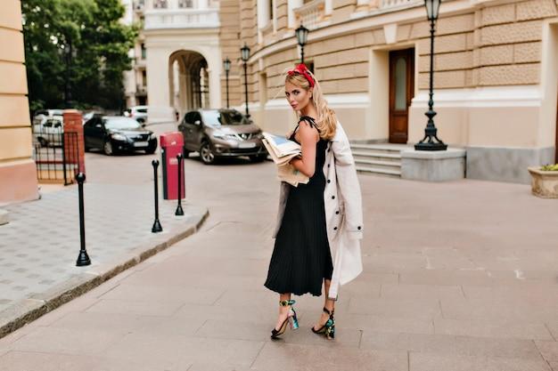 Retrato de corpo inteiro de uma mulher loira inspirada em um vestido preto olhando por cima do ombro e sorrindo gentilmente na praça da cidade