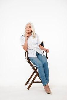 Retrato de corpo inteiro de uma mulher madura pensativa sentado