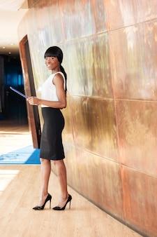 Retrato de corpo inteiro de uma mulher sorridente em pé com uma pasta no escritório e olhando para a frente