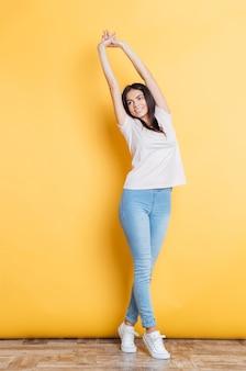 Retrato de corpo inteiro de uma mulher sorridente, estendendo as mãos na parede amarela