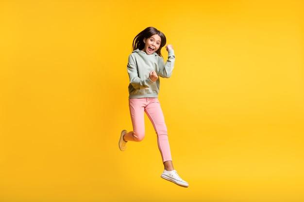 Retrato de corpo inteiro de uma pupila de cabelo castanho pulando com as mãos em punho, sim, felicidade isolada em um fundo de cor amarela