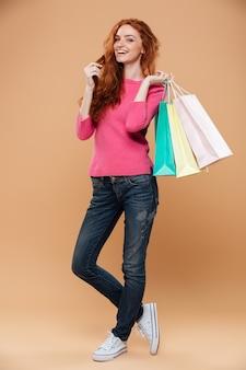 Retrato de corpo inteiro de uma ruiva alegre bonita com sacos de compras