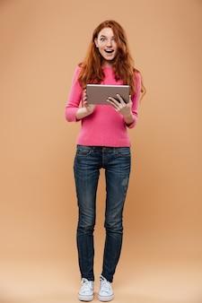 Retrato de corpo inteiro de uma ruiva bonita animado segurando o tablet