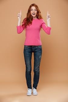 Retrato de corpo inteiro de uma ruiva jovem animado apontando para cima com os dedos