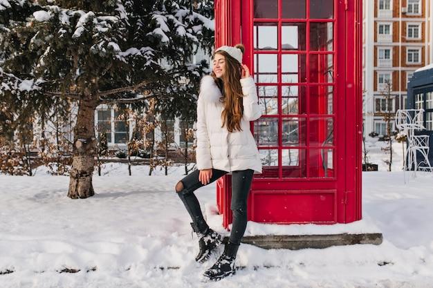 Retrato de corpo inteiro de uma senhora entusiasmada com penteado longo, posando perto de uma cabine telefônica vermelha no inverno. foto ao ar livre de uma mulher bonita caucasiana com chapéu branco aproveitando as férias de dezembro na inglaterra.