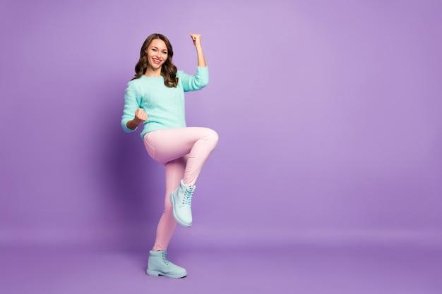 Retrato de corpo inteiro de uma senhora louca e encantada celebrando o time de futebol que venceu a liderança em uma competição esportiva, use botas de calça rosa de pulôver macio e macio.