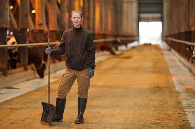 Retrato de corpo inteiro de uma trabalhadora sorrindo para a câmera e segurando uma pá enquanto limpa o galpão de vacas na fazenda da família, copie o espaço