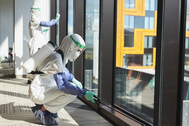 Retrato de corpo inteiro de vista lateral de duas trabalhadoras vestindo roupas anti-perigosas, desinfetando janelas em prédio de escritórios,