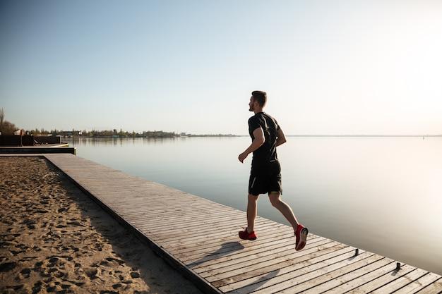 Retrato de corpo inteiro de vista traseira de um jovem esportista correndo