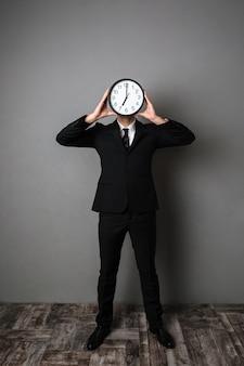 Retrato de corpo inteiro do empresário em terno preto, segurando o grande relógio na frente do rosto