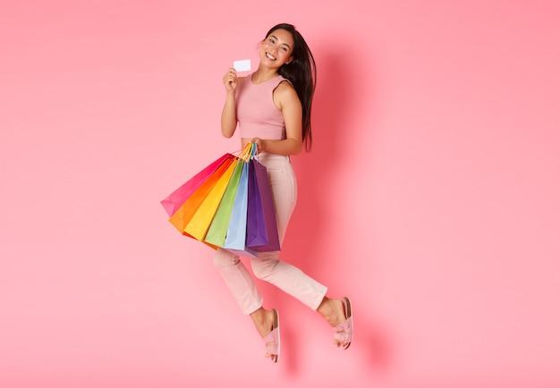 Retrato de corpo inteiro do glamour bobo e fofo que uma garota asiática adora desperdiçar dinheiro em lojas