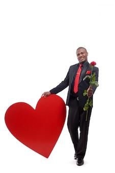 Retrato de corpo inteiro do homem africano feliz dando uma rosa vermelha