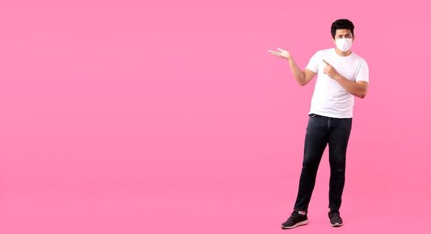 Retrato de corpo inteiro do homem asiático bonito vestindo uma máscara está doente apontando o dedo isolado no fundo rosa no estúdio com espaço de cópia.