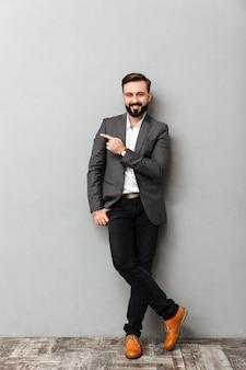 Retrato de corpo inteiro do homem atraente, posando na câmera com um sorriso largo, apontando o dedo indicador de lado, isolado sobre o cinza
