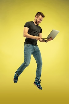 Retrato de corpo inteiro do homem pulando feliz com dispositivos isolados em amarelo
