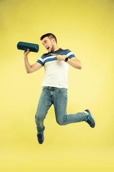 Retrato de corpo inteiro do homem pulando feliz com gadgets em amarelo