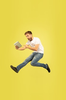 Retrato de corpo inteiro do homem pulando feliz em fundo amarelo