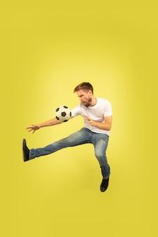 Retrato de corpo inteiro do homem pulando feliz isolado no amarelo