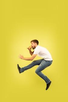 Retrato de corpo inteiro do homem pulando feliz na parede amarela