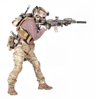 Retrato de corpo inteiro do jogador de airsoft em camisa xadrez, usando uniforme camuflado, capacete com fone de ouvido de rádio tático, armadura corporal, mirando com rifle de serviço replica estúdio tiro isolado no branco