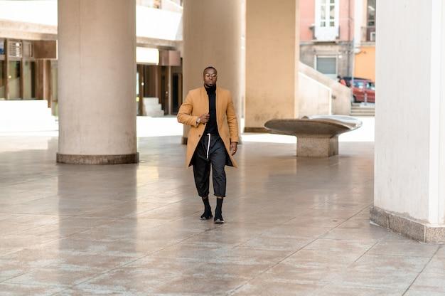 Retrato de corpo inteiro do jovem empresário negro andando na cidade.