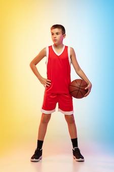 Retrato de corpo inteiro do jovem jogador de basquete de uniforme na parede gradiente