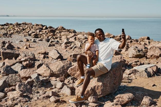 Retrato de corpo inteiro do jovem pai afro-americano brincando com o filho fofo na praia e tomando selfi ...