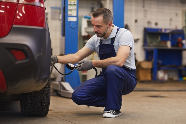 Retrato de corpo inteiro do mecânico de automóveis verificando a pressão dos pneus durante a inspeção do veículo na oficina, copie o espaço