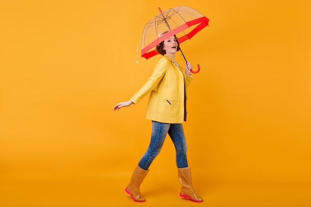 Retrato de corpo inteiro do modelo feminino caucasiano com jaqueta amarela e sapatos de borracha. foto de estúdio de garota despreocupada com cabelos ondulados dançando com guarda-chuva.