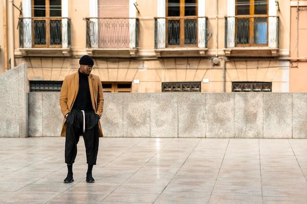 Retrato de corpo inteiro em um homem negro bonito em um terno elegante de pé com as mãos no bolso. vida urbana da cidade em segundo plano.