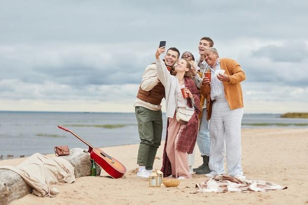 Retrato de corpo inteiro franco de diversos grupos de amigos tirando uma foto de selfie na praia no outono, copie o espaço