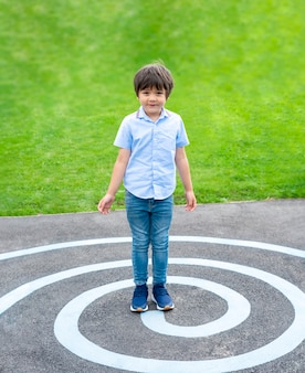 Retrato de corpo inteiro garoto parado na linha do círculo no asfalto