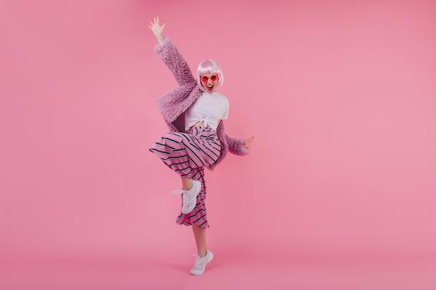 Retrato de corpo inteiro interior de uma agradável garota glamourosa de cabelo rosa. jovem feliz na peruca dançando com tênis branco e rindo