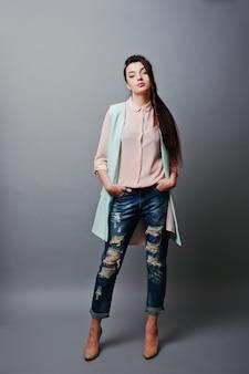 Retrato de corpo inteiro jovem menina morena vestindo blusa rosa, jaqueta turquesa, jeans rasgados e sapatos creme