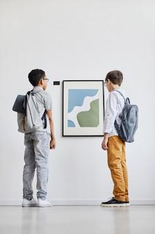 Retrato de corpo inteiro mínimo de dois alunos olhando pinturas abstratas na galeria de arte moderna, copie o espaço
