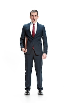 Retrato de corpo inteiro ou de corpo inteiro de empresário ou diplomata com pasta no fundo branco do estúdio. jovem surpreso de terno, gravata vermelha em pé no escritório. negócios, carreira, conceito de sucesso.