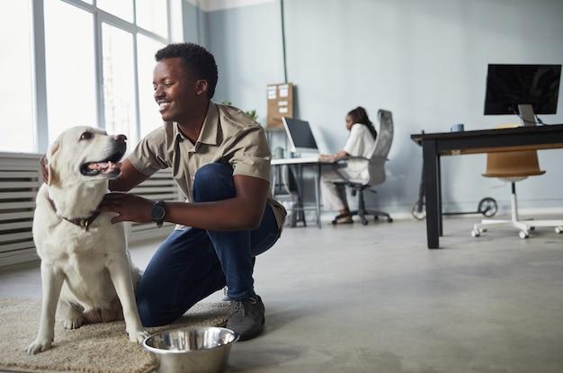 Retrato de corpo inteiro sorridente homem afro-americano acariciando cachorro enquanto trabalhava em um escritório que aceita animais de estimação.
