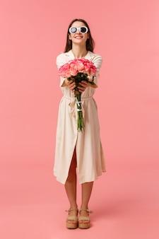 Retrato de corpo inteiro vertical atraente atrevida e elegante mulher morena dando flores para a namorada, estendendo as mãos para a realização de belo buquê de rosas, em pé parede rosa