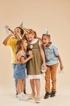 Retrato de corpo inteiro vertical de um grupo diversificado de crianças usando chapéus de festa, gritando ao microfone enquanto posam em bege